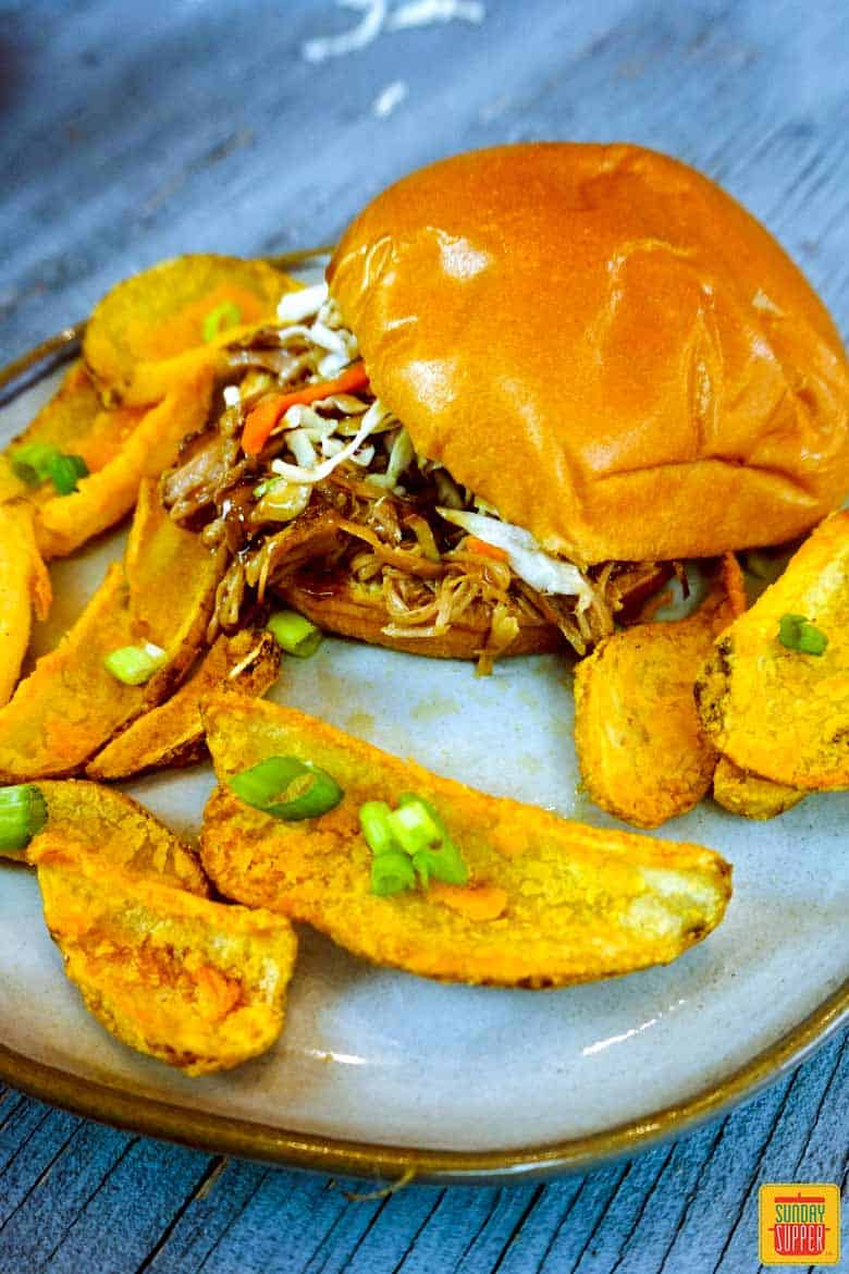 Pulled pork sandwich on a plate with potato wedges