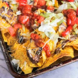 Steak nachos up close on a baking sheet