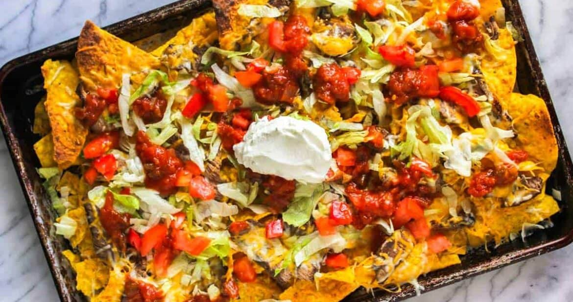 Steak nachos in a sheet pan with a dollop of sour cream