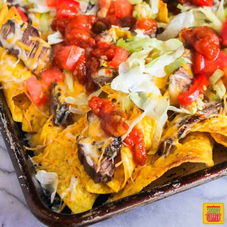Steak nachos in a sheet pan with tomatoes and lettuce