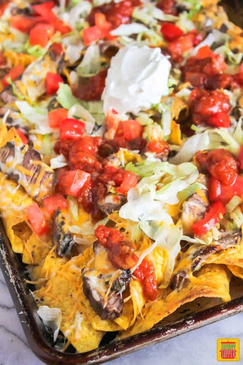 Nachos with steak tomato and lettuce in a sheet pan