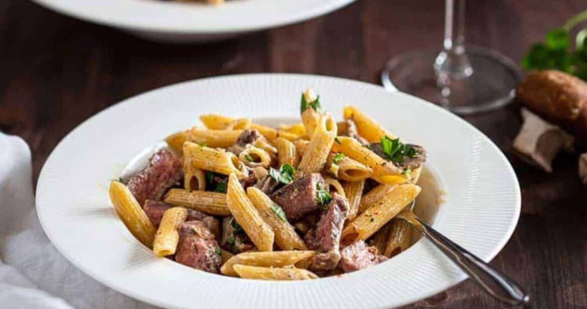 Valentine's Dinner Ideas: Creamy Penne Pasta in a white dish with a fork and wine glass