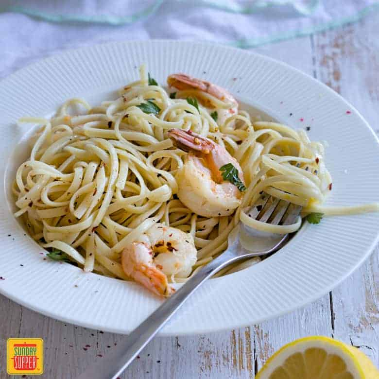 Shrimp Scampi Linguine served on a white plate with a fork for valentine's dinner ideas