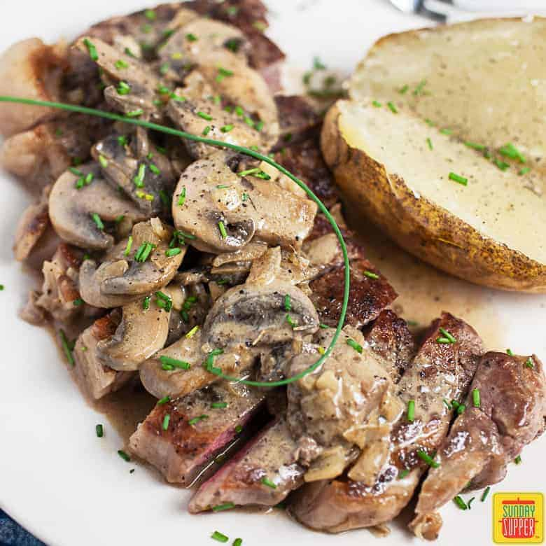 Valentine's Dinner Ideas: Steak Diane on a plate with potatoes and fresh herbs