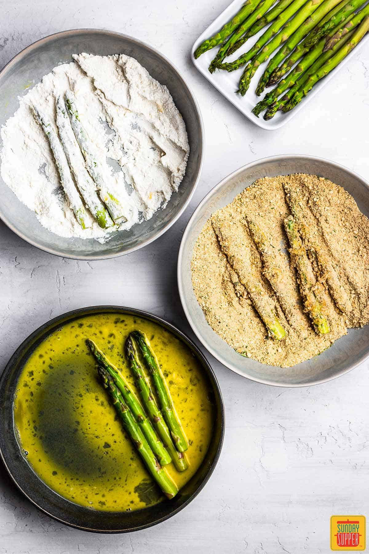 Asparagus in egg, in flour, and in breadcrumbs for asparagus fries
