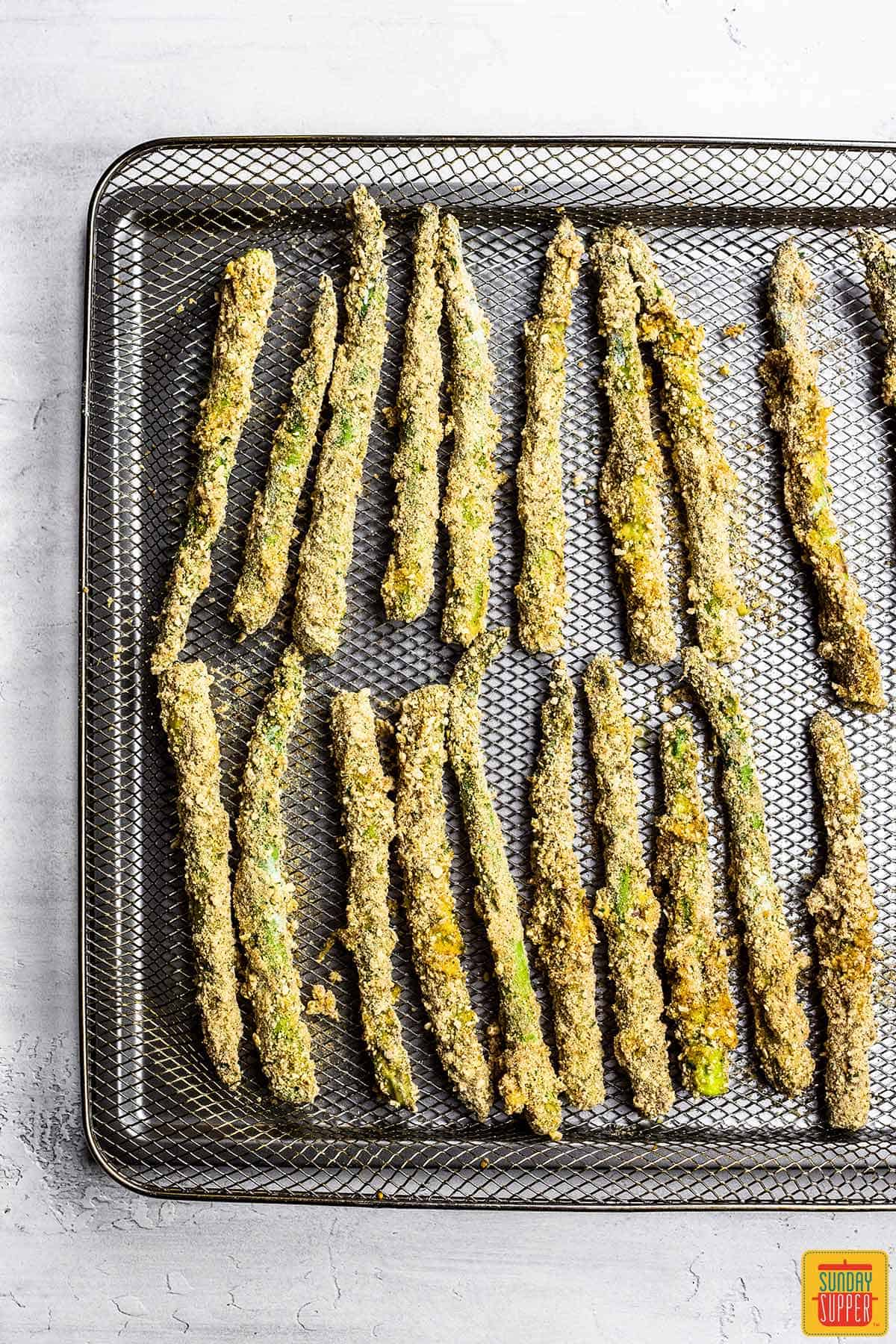 Placing asparagus fries on air fryer rack