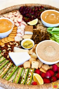 Dips, celery sticks, cheese, nuts, and crackers on a board