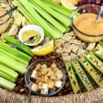 Close up of charcuterie board with celery sticks and dips in bowls