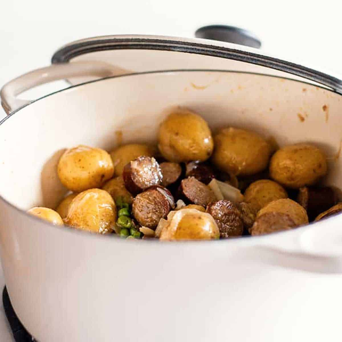 Smothered potatoes and sausage in a white Dutch oven