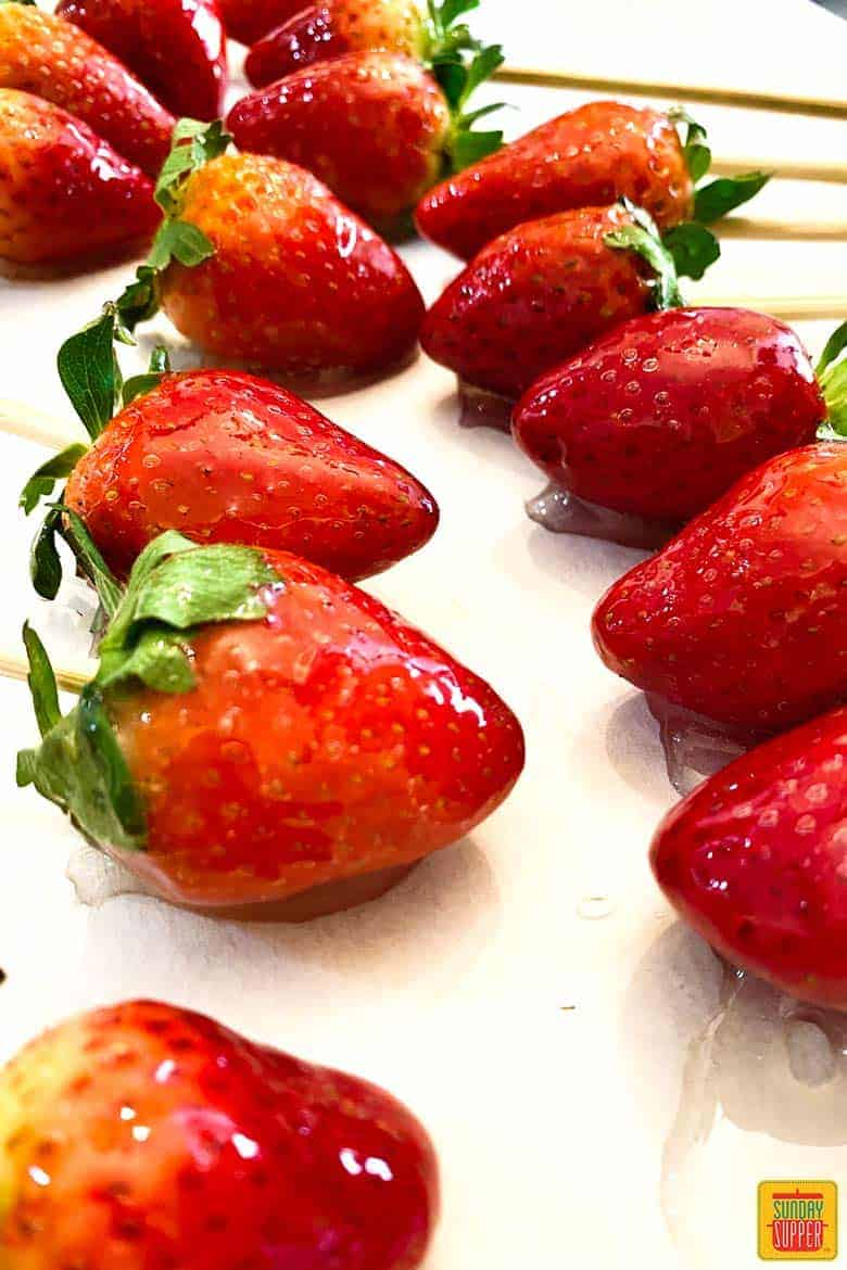 Three rows of candied strawberries on parchment paper
