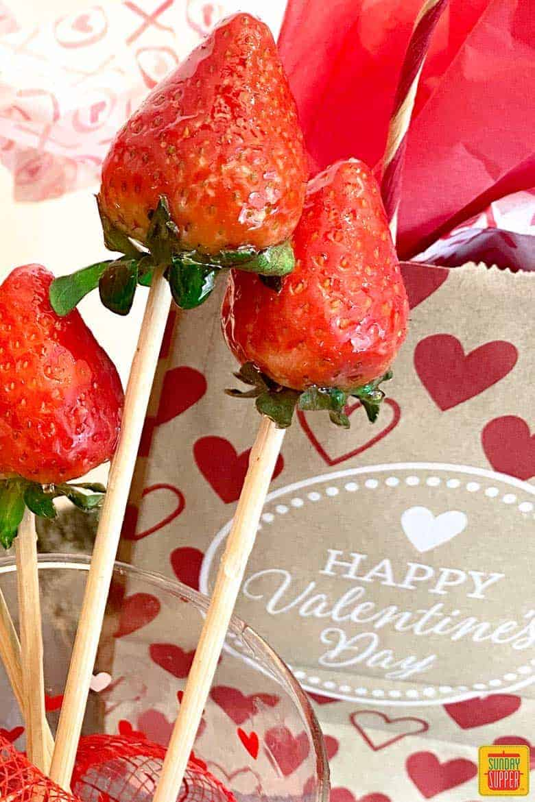 Three candied strawberries on skewers in front of a Valentine's bag