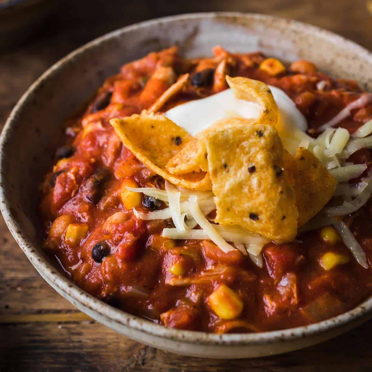 Chicken chili in a gray bowl with Frito chips on top