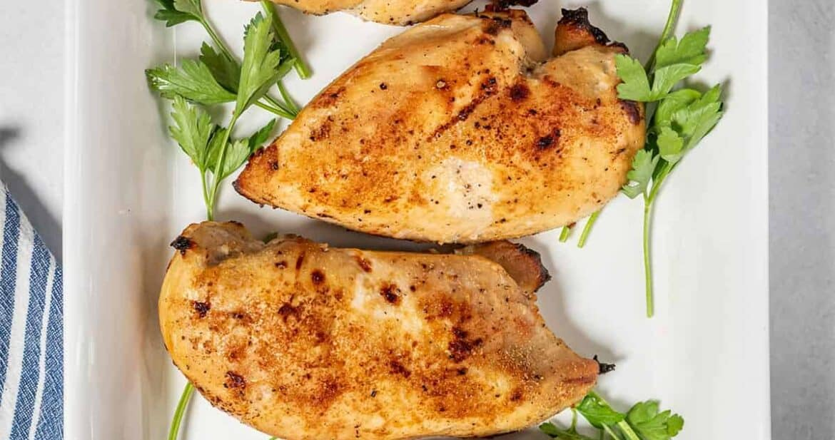 Four buttermilk roast chicken breasts on a white platter with herbs