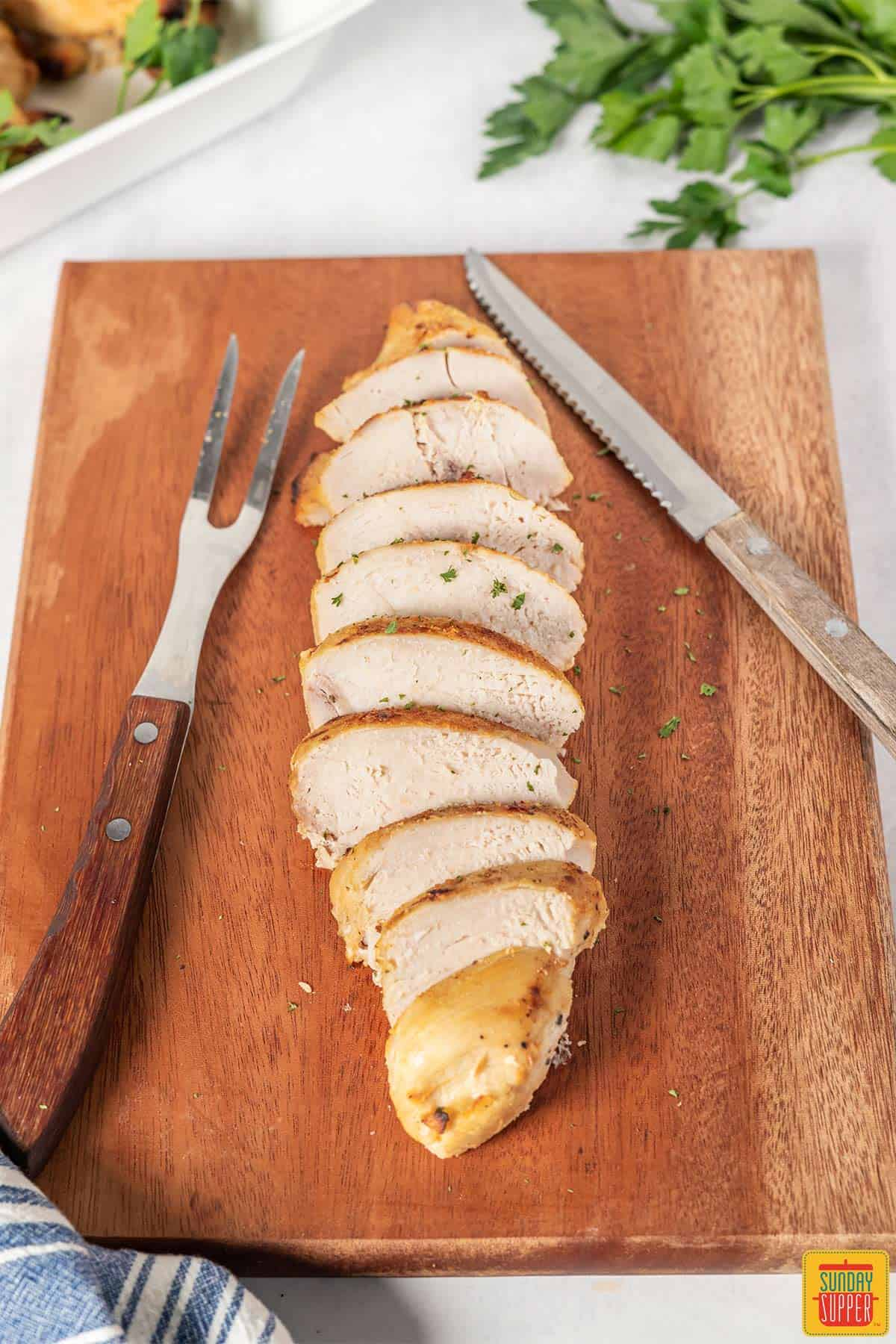 Buttermilk roast chicken on a cutting board with a serving fork and knife