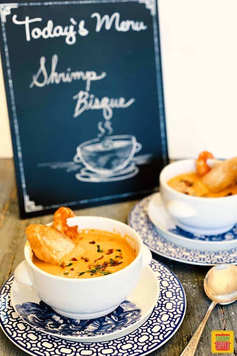Shrimp bisque in two bowls on blue and white plates near a chalkboard sign reading 'Today's Menu - Shrimp Bisque'