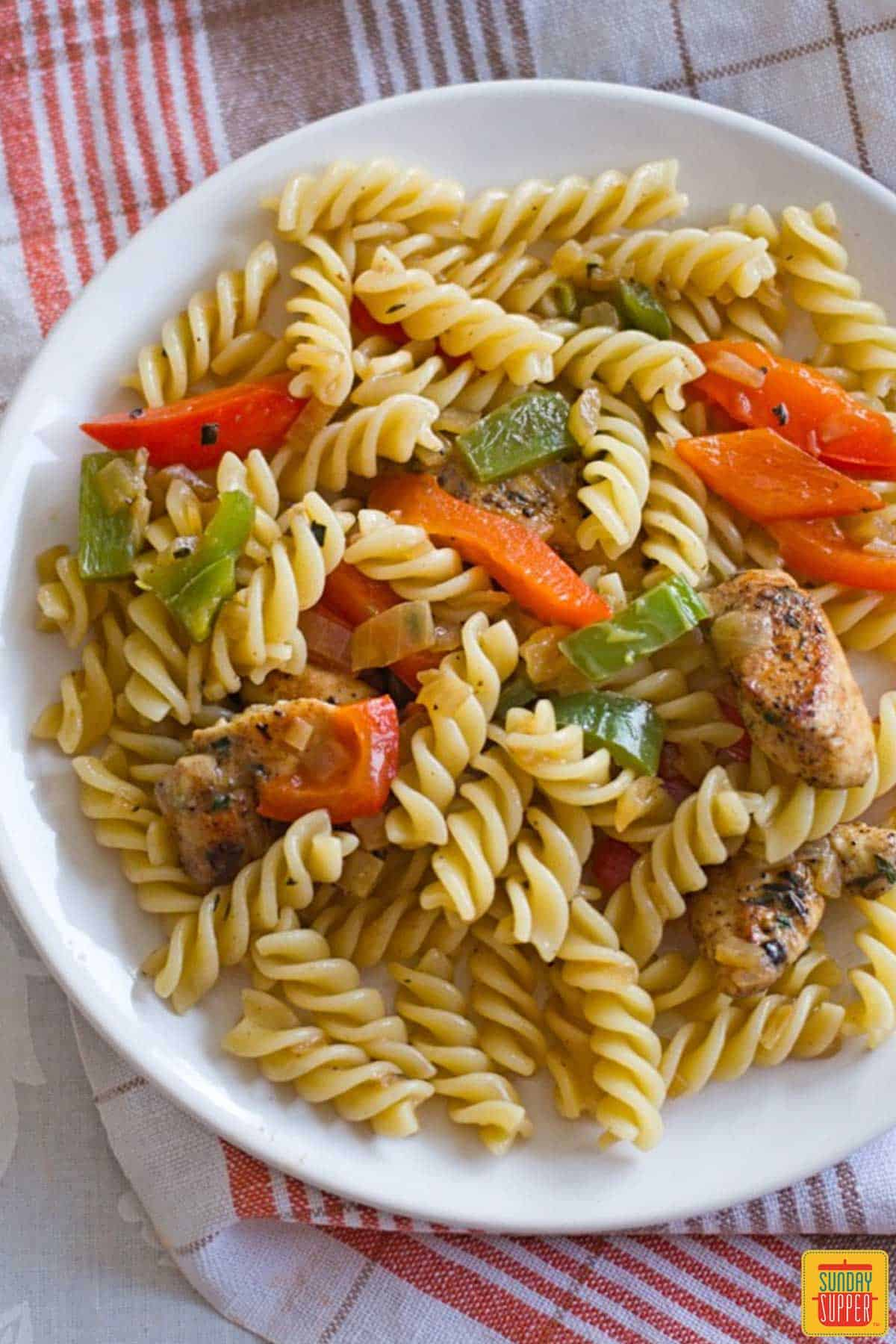 A white plate with rasta pasta and jerk chicken