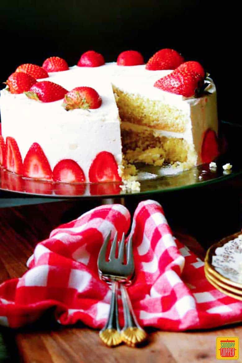 strawberry lemon cake on a cake stand with a fork and napkin