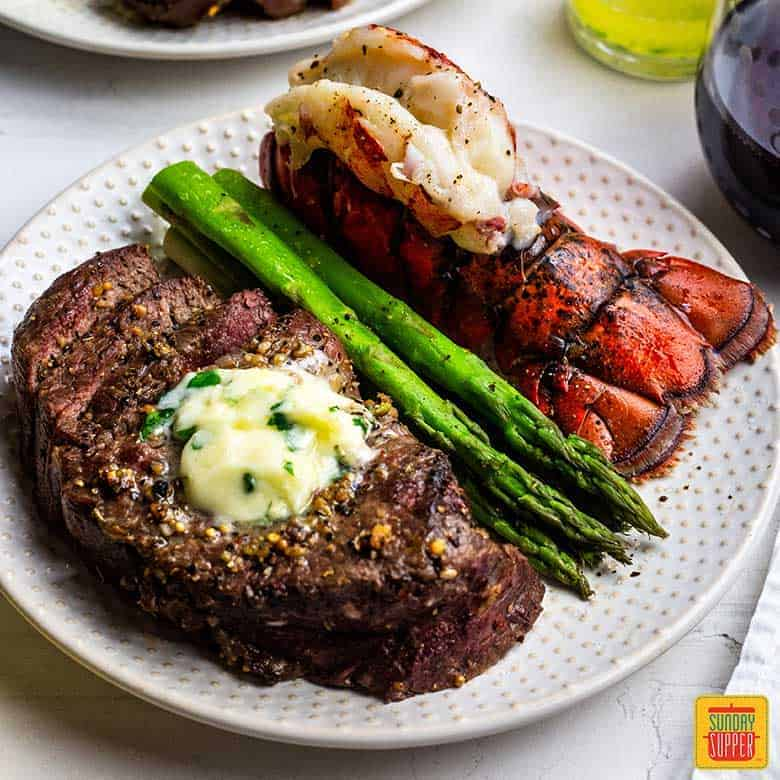 White plate with air fried steak and fried lobster tail with a side of steamed asparagus for Valentine's Dinner Ideeas