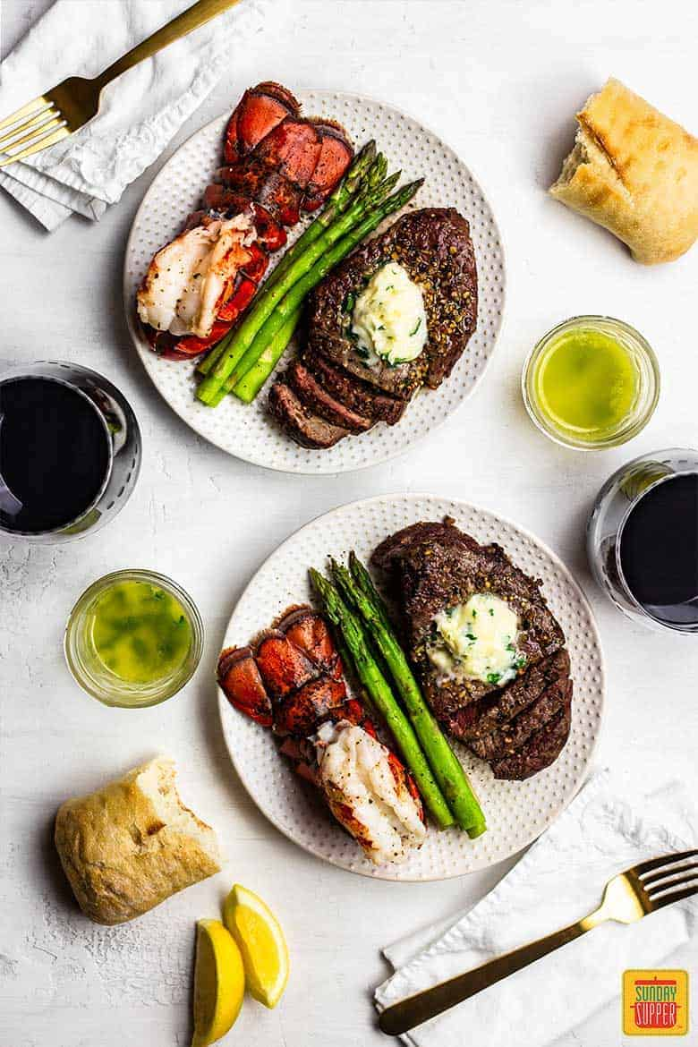 Two plates of surf and turf recipe with air fried steak and fried lobster tails and a side of steamed asparagus and wine, plus two bowls of garlic butter for dipping
