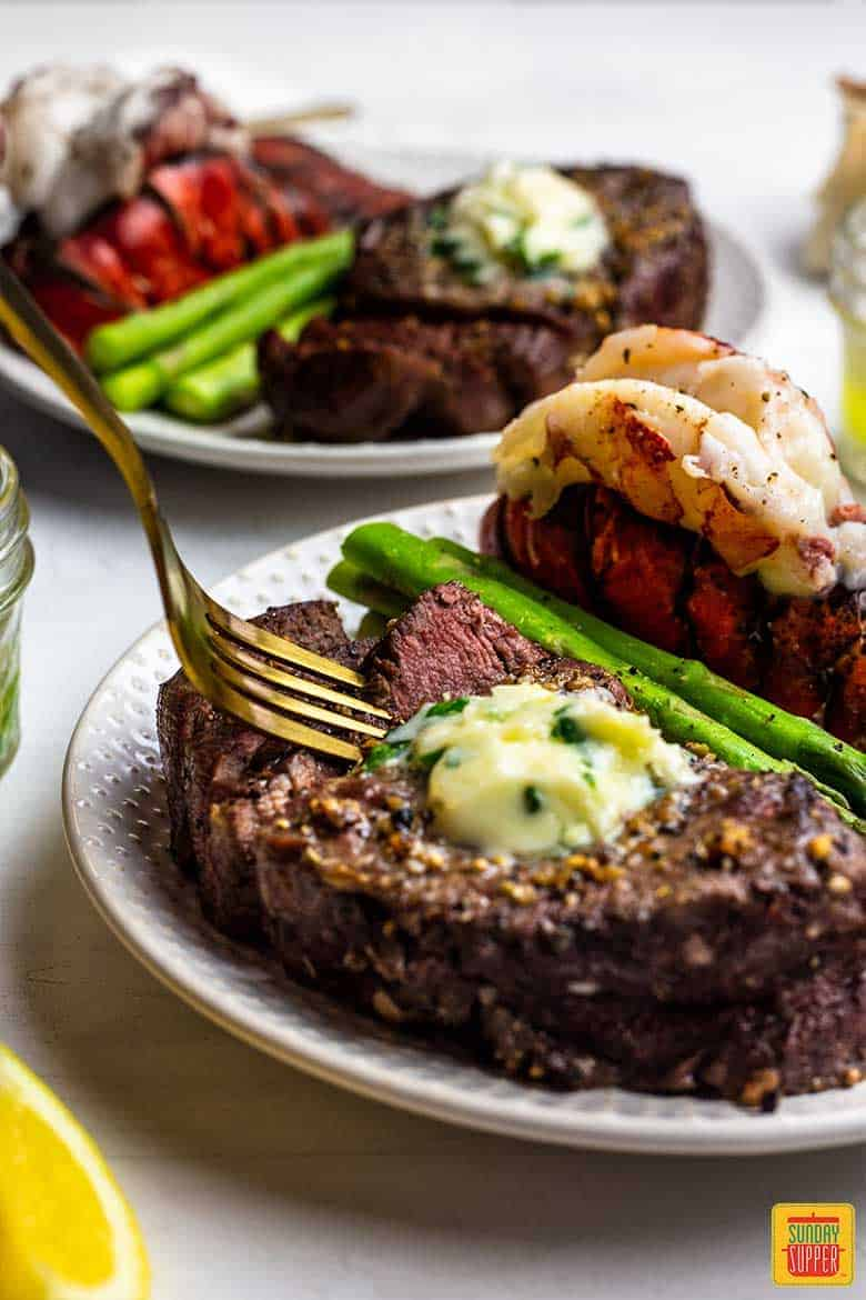 A fork digging into air fryer surf and turf recipe