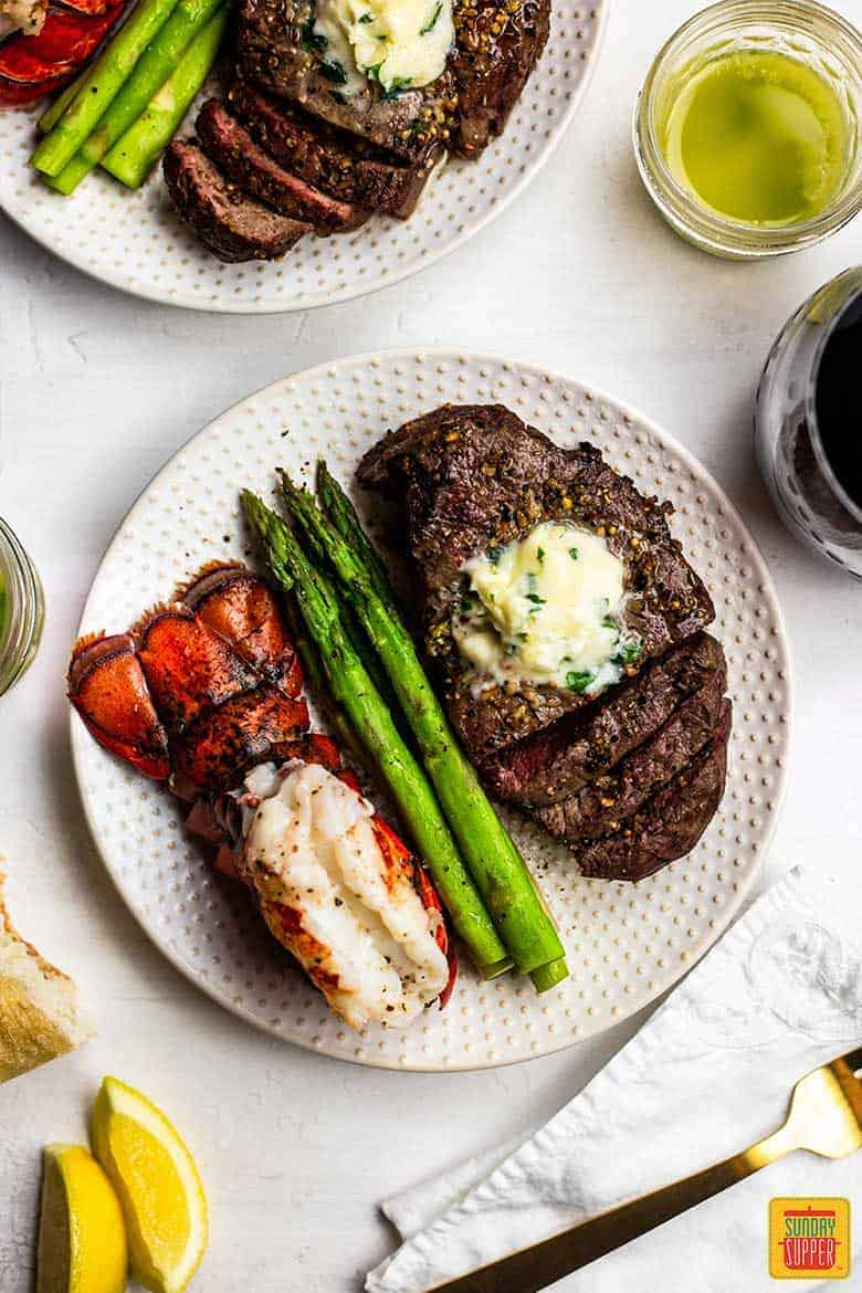 Two white plates of air fryer surf and turf recipe with air fryer steak, lobster tails, steamed asparagus, and a bowl of garlic butter sauce
