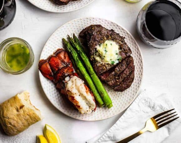 Plate with air fried steak and fried lobster tail with a side of steamed asparagus and a glass of wine