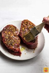 Brushing steak with garlic butter for air fried steak surf and turf recipe