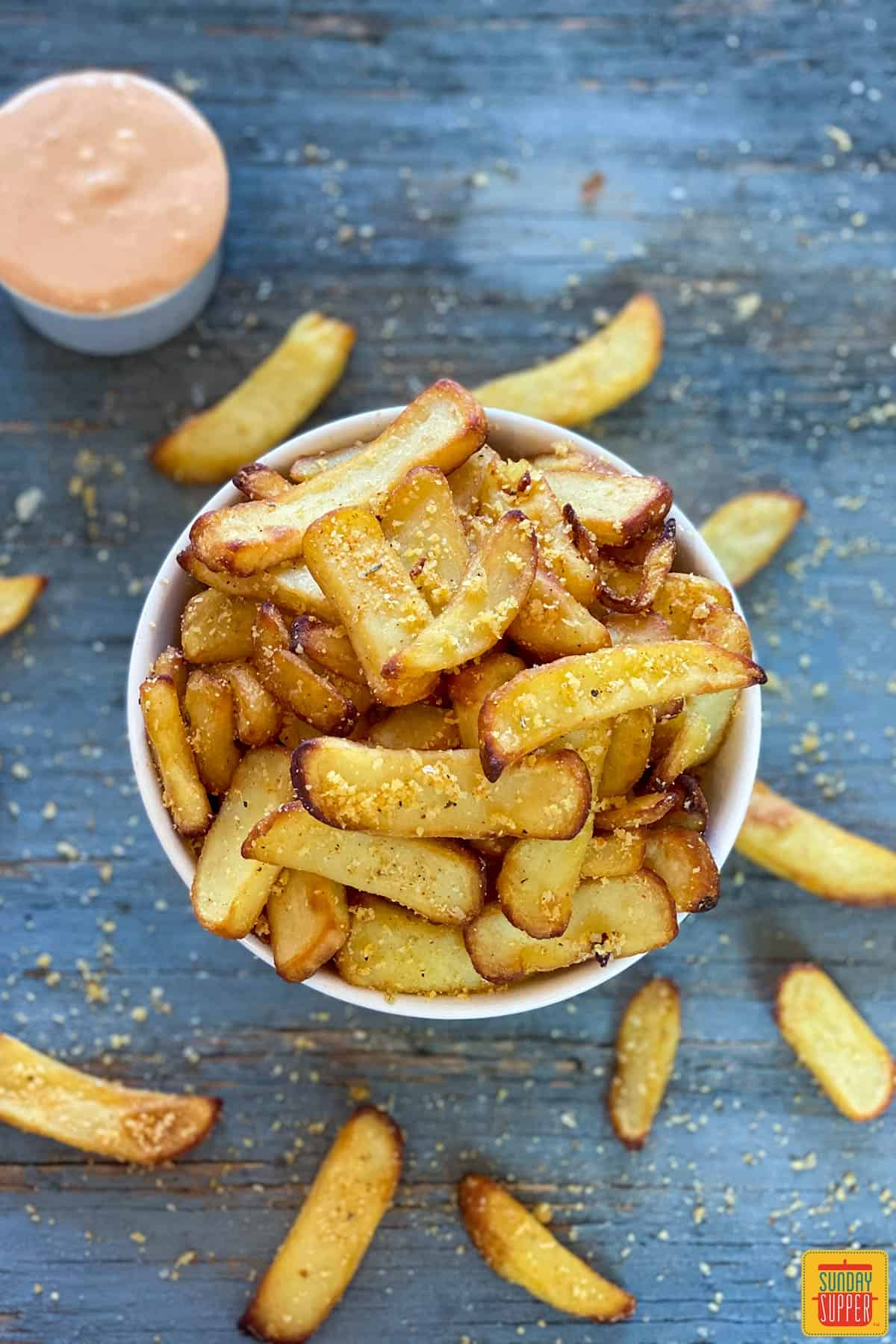 Fries scattered around a bowl of french fries