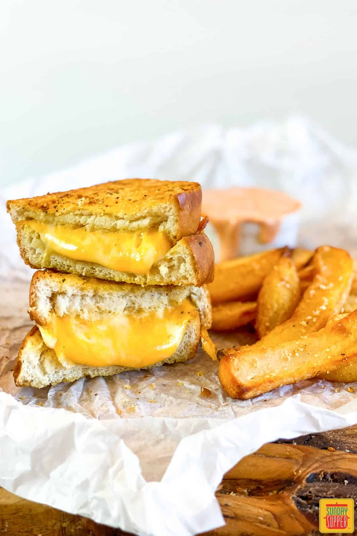 Air fryer grilled cheese cut in half next to some fries