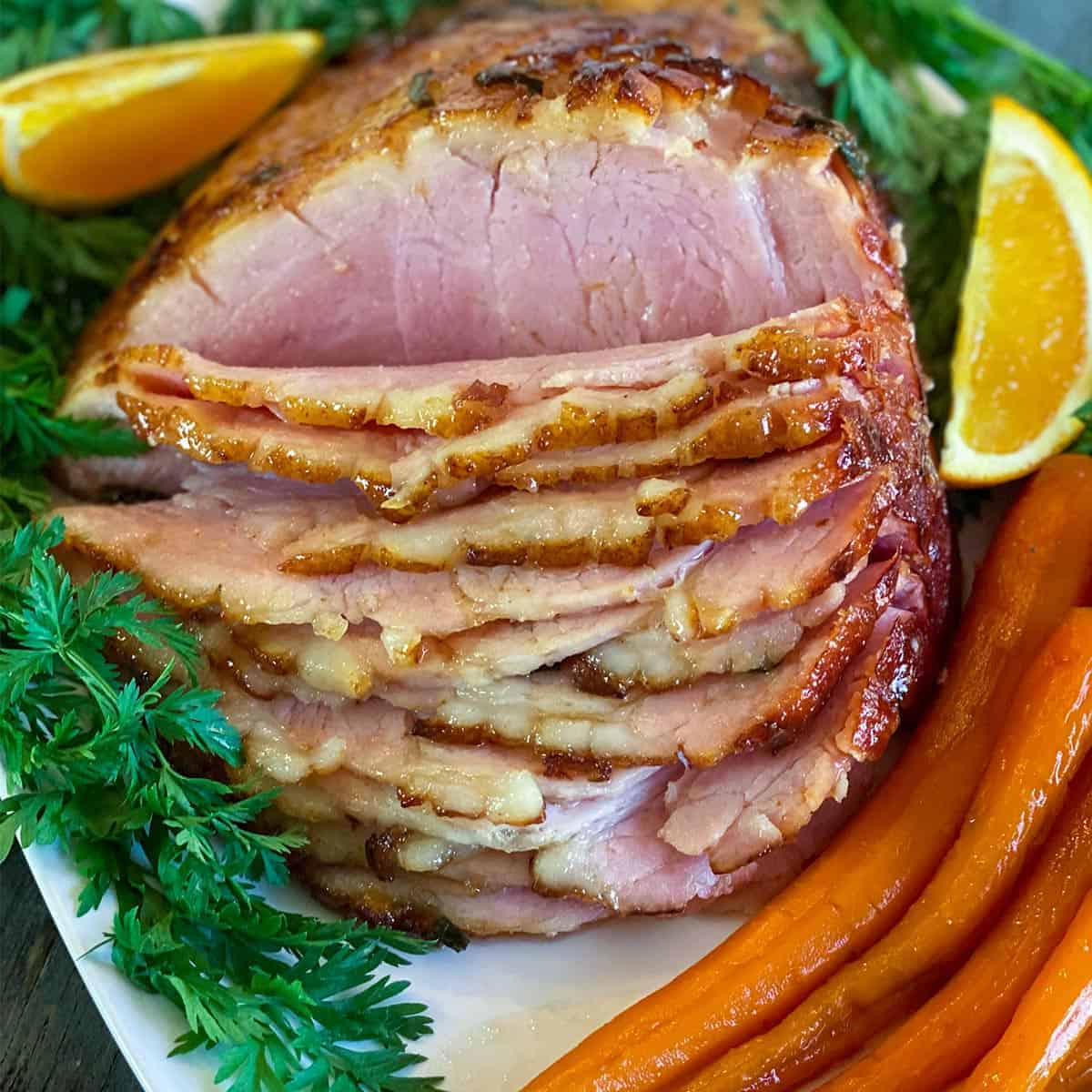 Close up of air fryer ham with citrus and candied carrots