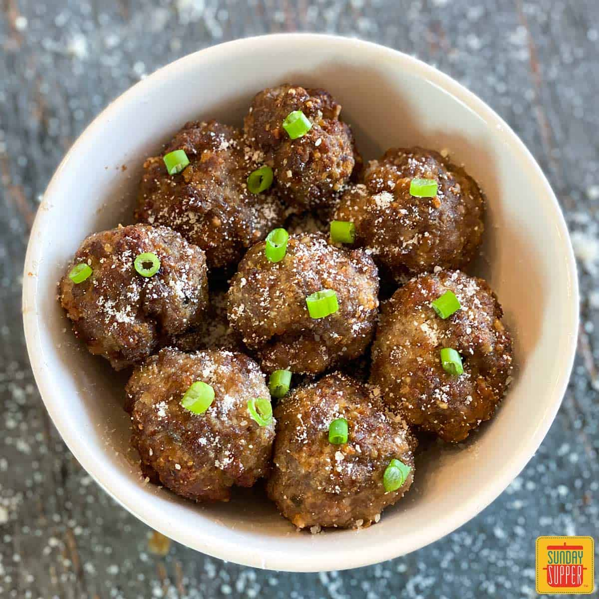 Close up of air fryer meatballs with green onions in a white bowl