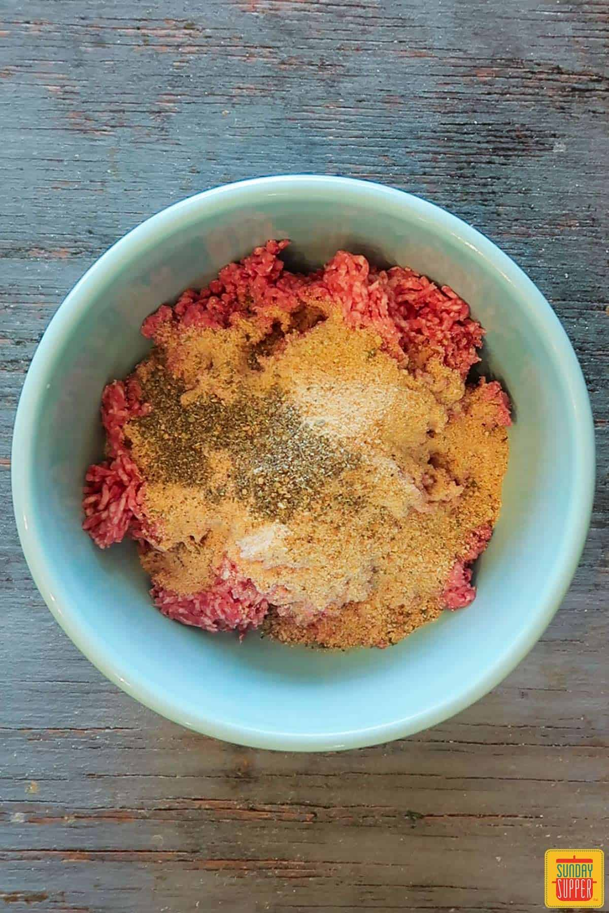 Dry spices on top of meatball mixture in bowl