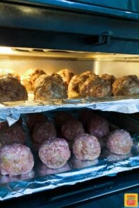 Two trays of air fryer meatballs in the air fryer to cook