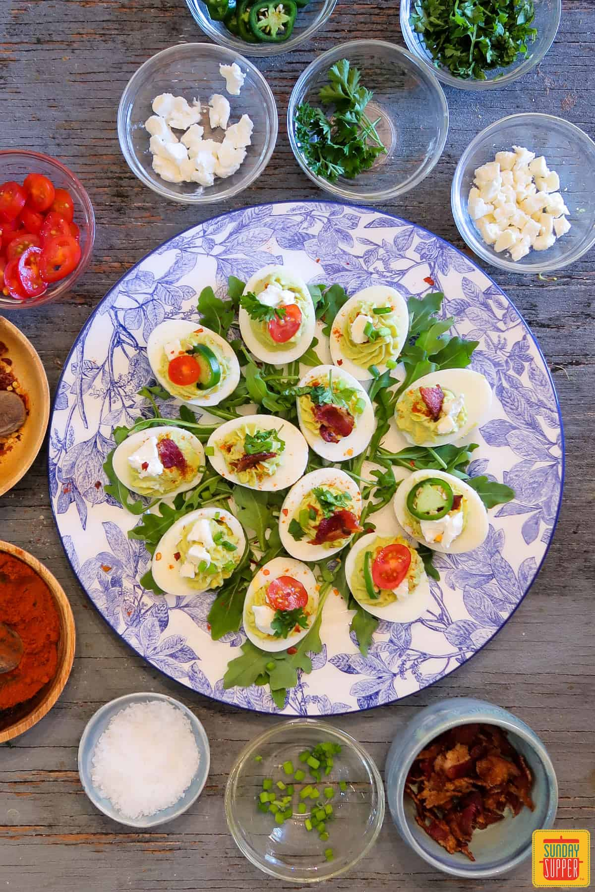 Avocado deviled eggs surrounded by toppings