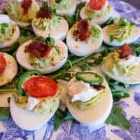 Close up of avocado deviled eggs on a white and blue floral plate