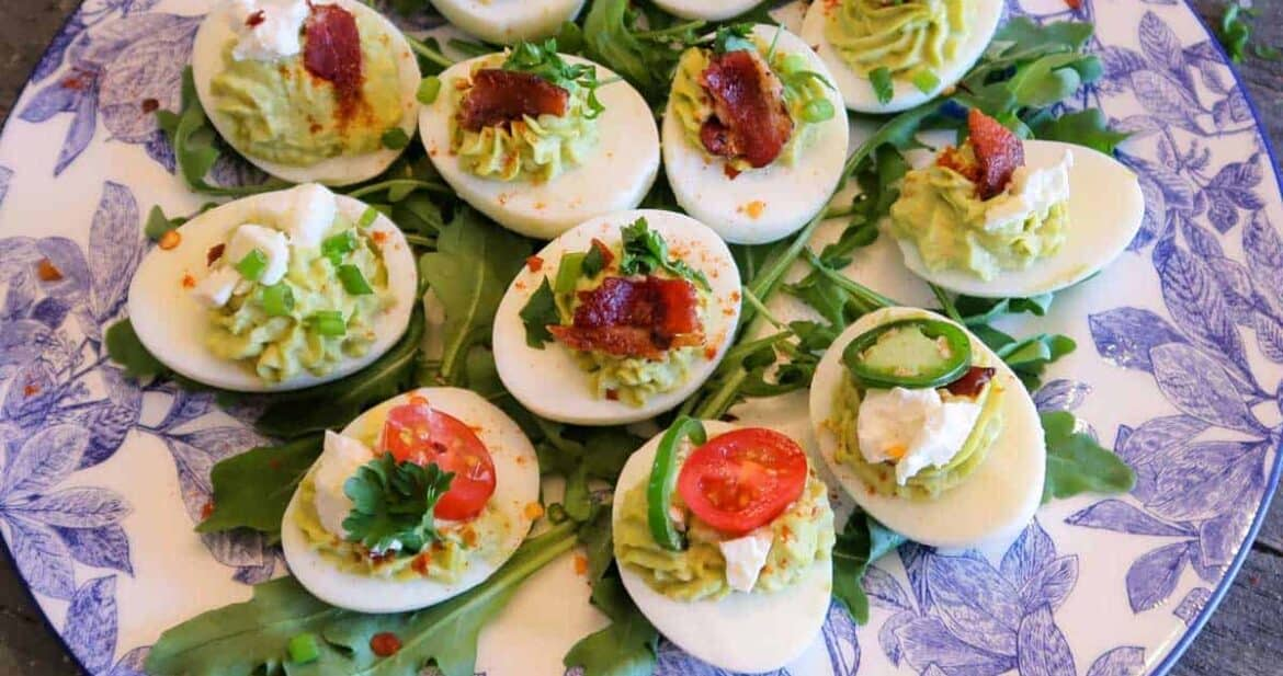 Close up of Avocado deviled eggs over a bed of greens on a white and blue floral plate