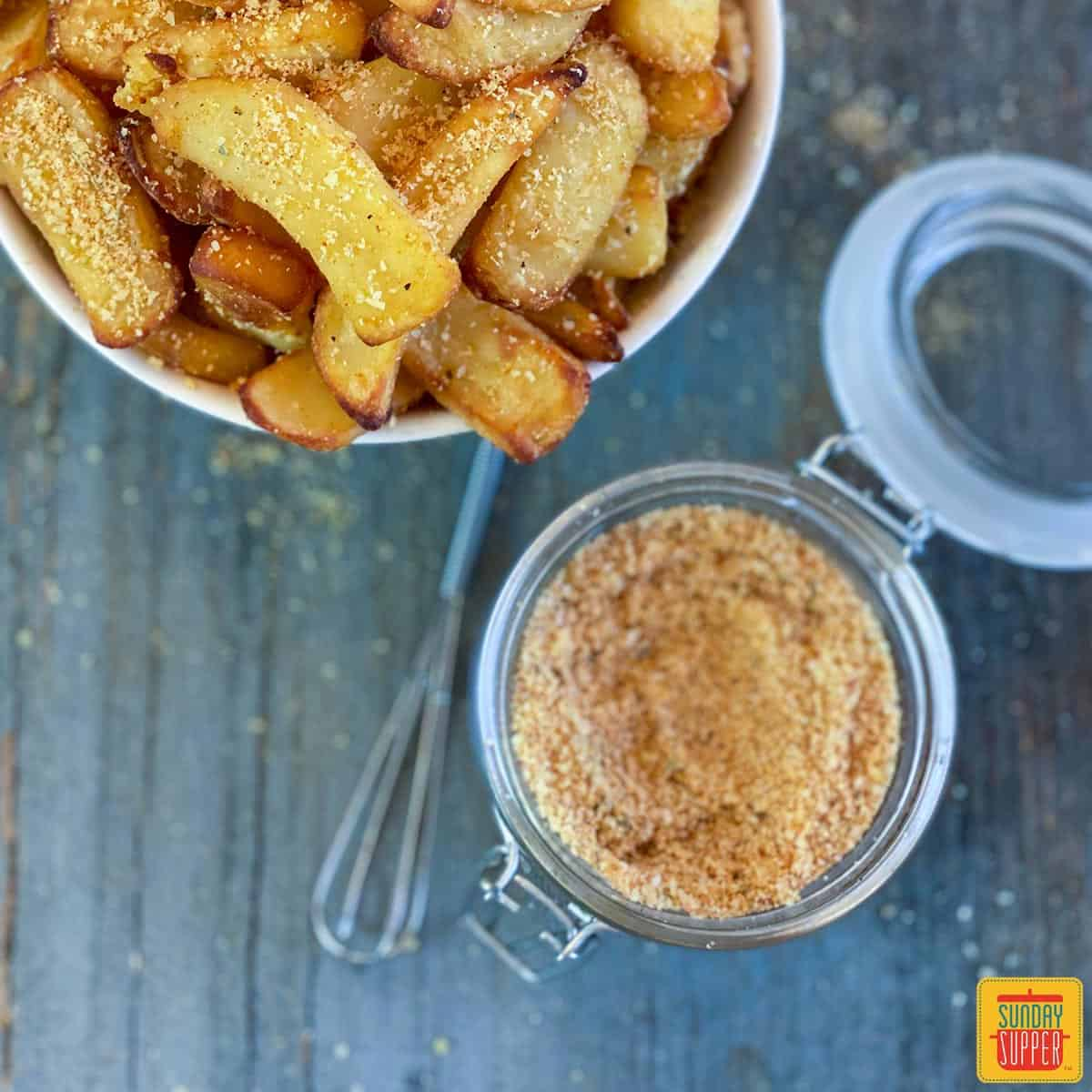 French fry seasoning in a jar next to air fryer fries in a bowl