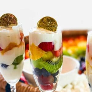 Three yogurt parfait glasses in front of rainbow charcuterie board