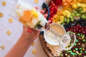 Yogurt on top of oranges and cantaloupe in fruit and yogurt parfait