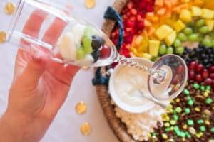 Adding yogurt to fruit yogurt parfait over kiwi