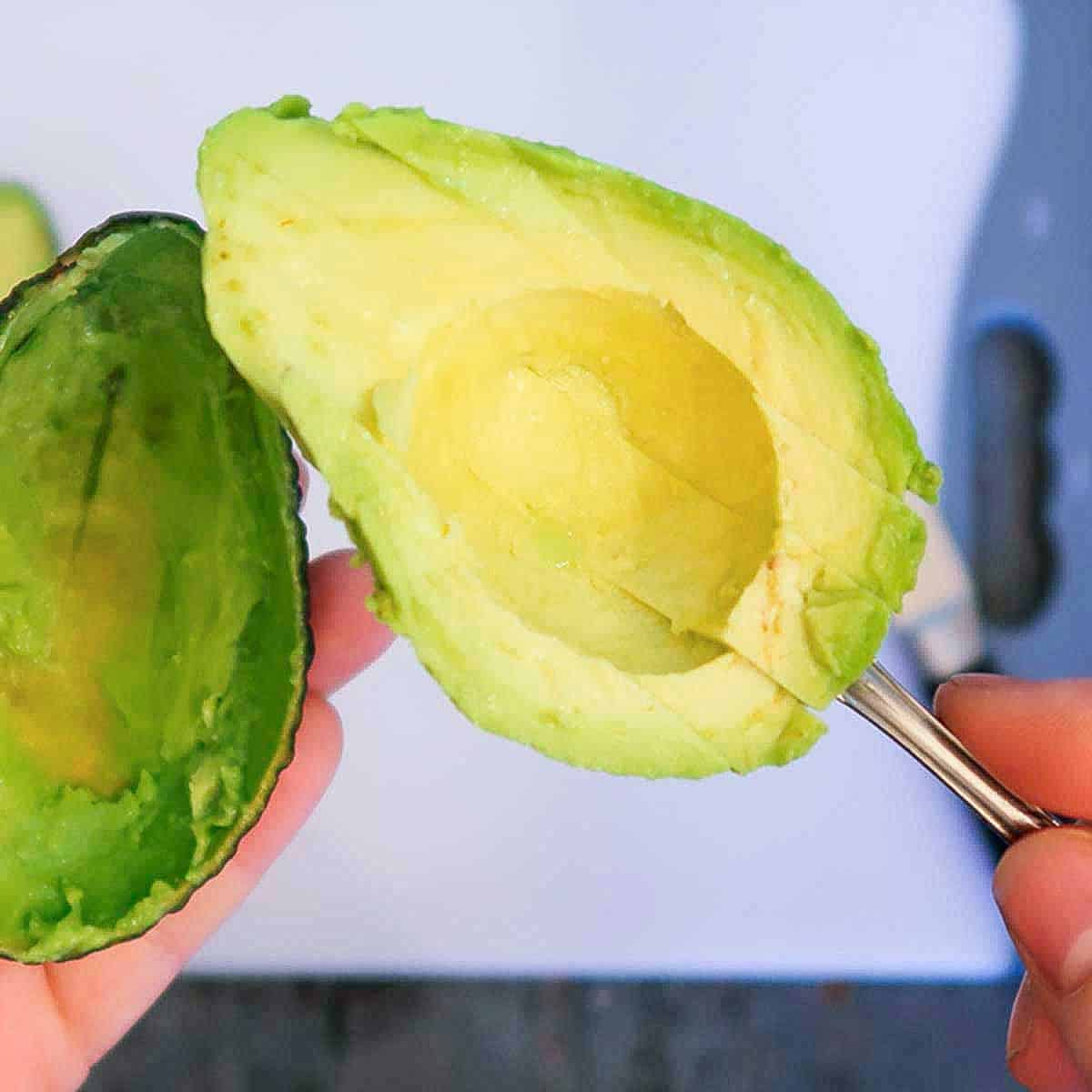 Half of an avocado cut into slices in a spoon