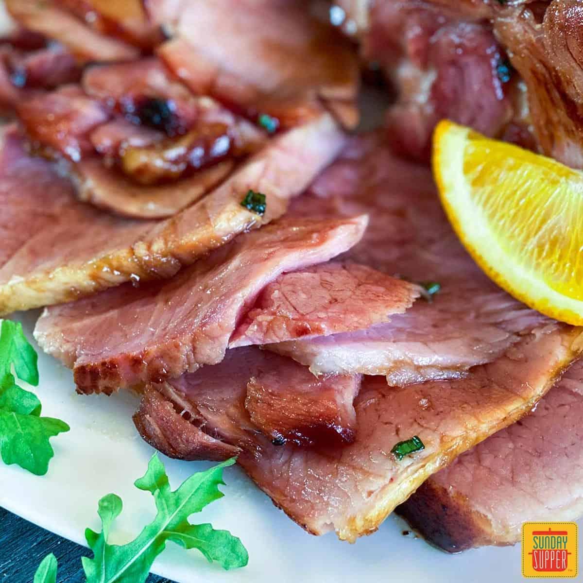 Sliced ham with oranges and arugula