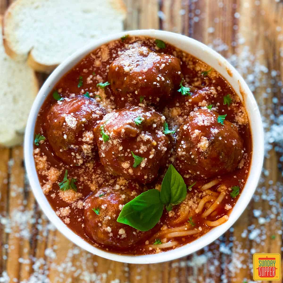 Meatball sauce recipe over meatballs and spaghetti in a white bowl