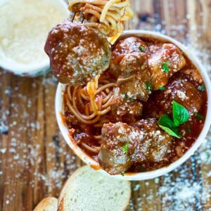 Lifting a meatball out of meatball sauce recipe over spaghetti in a white bowl
