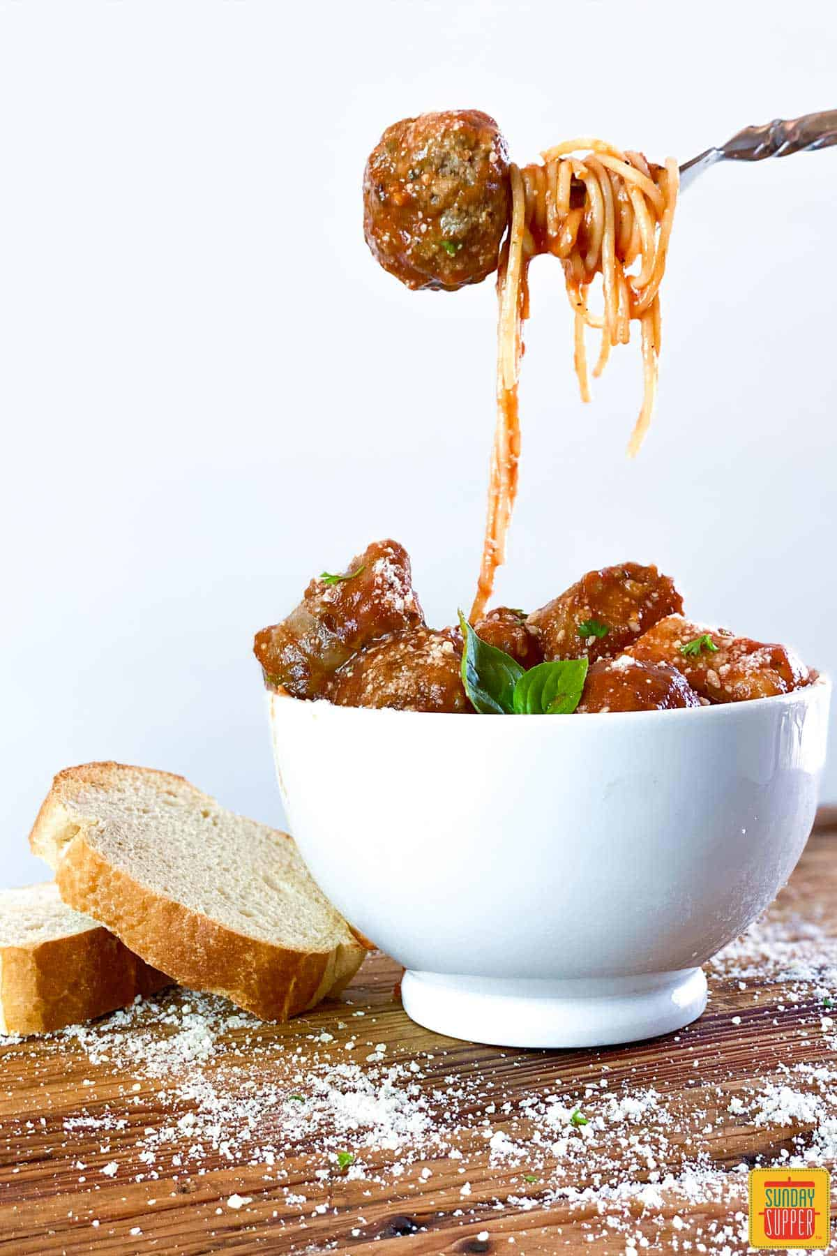 Lifting meatball out of spaghetti with sauce for meatballs in white bowl