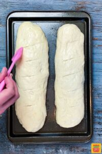 brushing egg wash on the top of homemade french bread dough