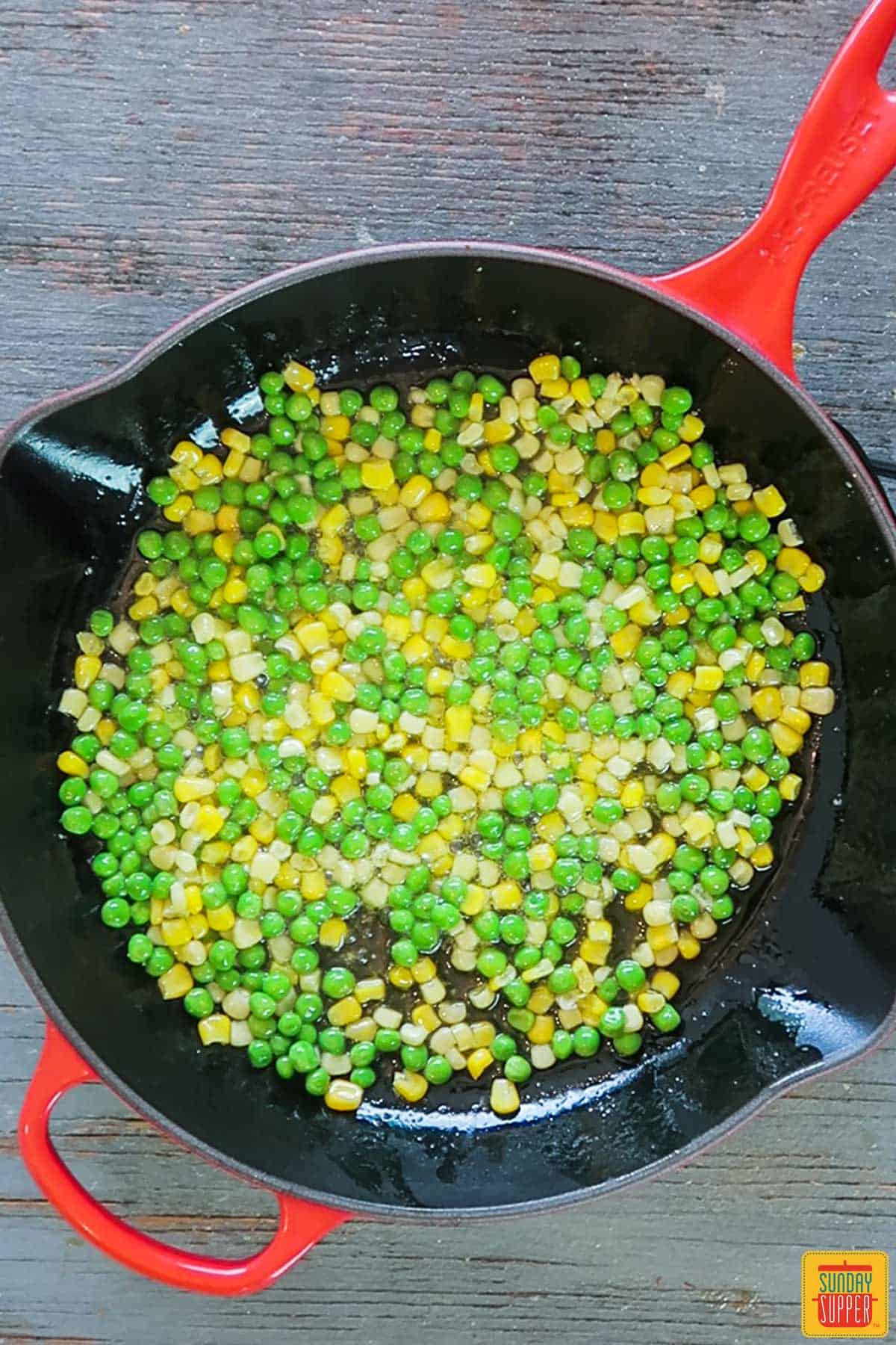 Cooking frozen peas and corn in skillet for pork fried rice