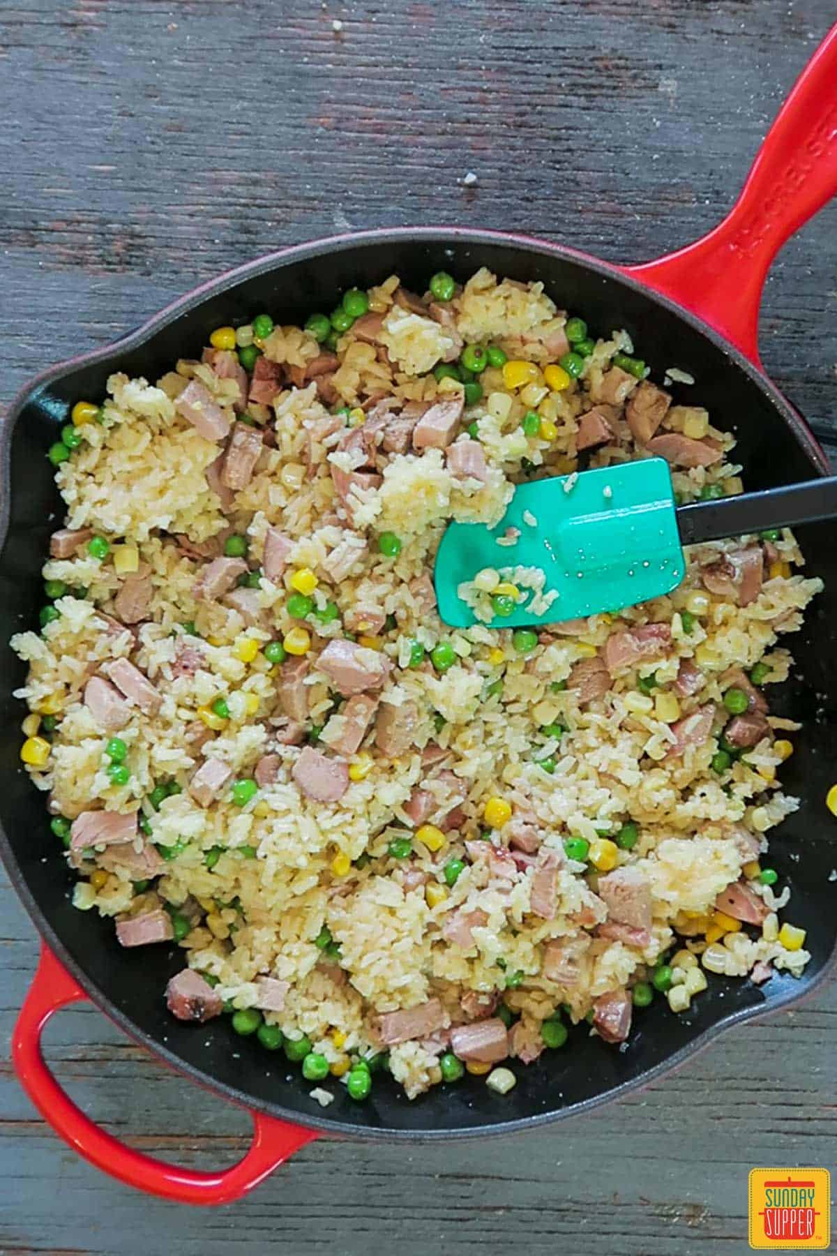 Stirring pork and fried rice in skillet