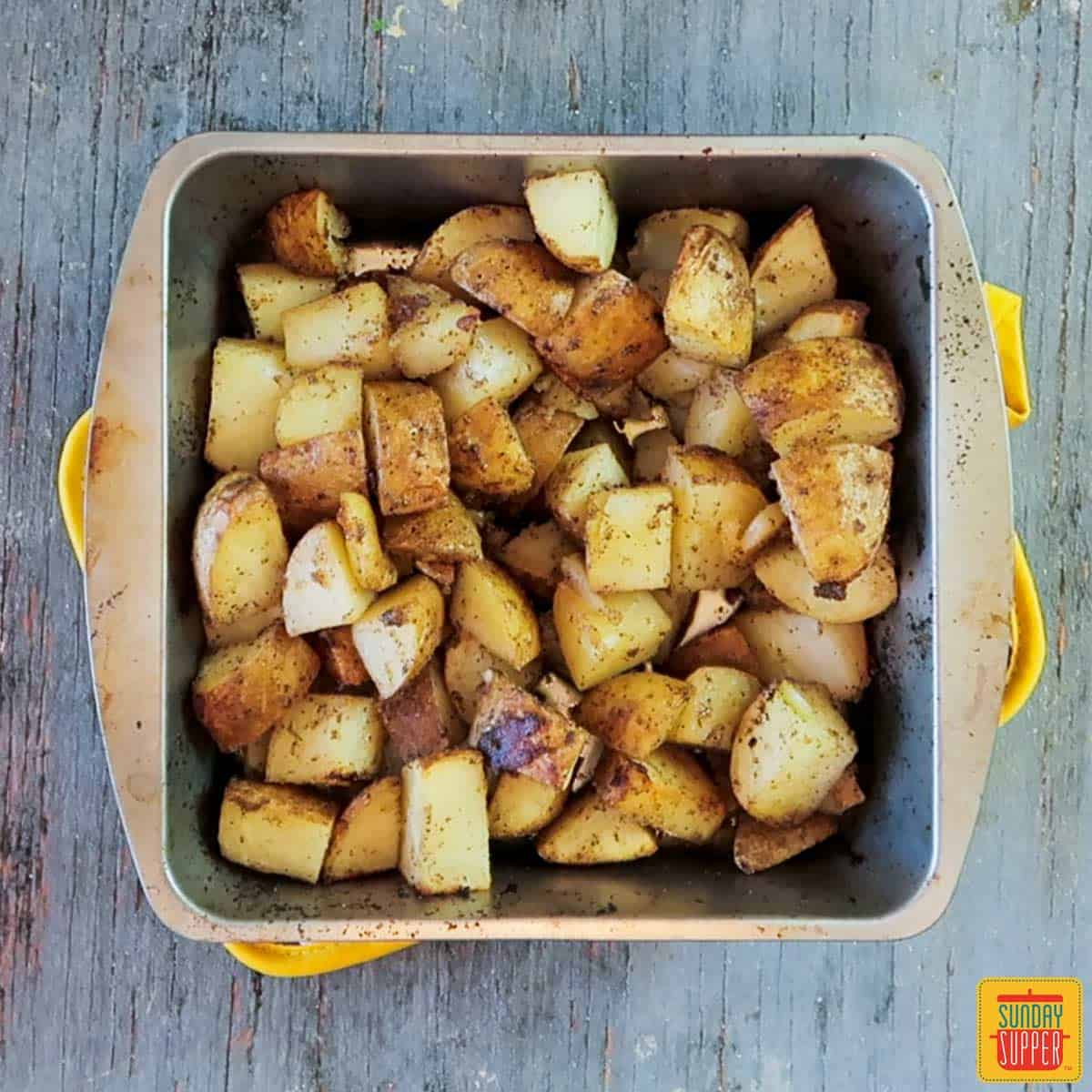Grilled potatoes recipe fresh off the grill in the baking tin resting on an oven towel