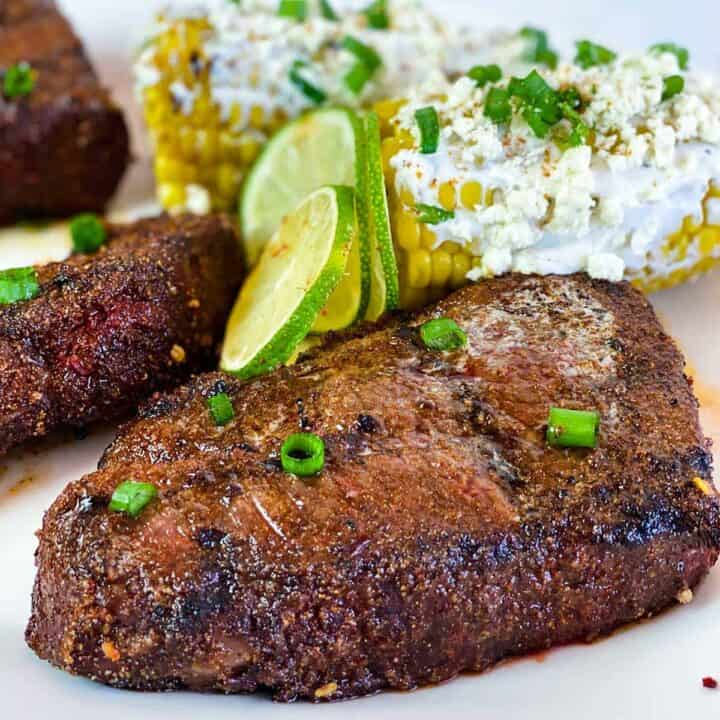Close up of grilled beef short ribs with lime wedges and elotes Mexicanos